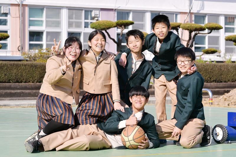Schüler der Jakcheon Middle School haben sich in ihren Hanbok-Uniformen auf dem Basketballplatz versammelt.